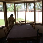 Jessica is staining the window sills that has been left dull when rain goes thru the window.